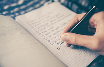 a hand holds a pen and checks off items on a list in a notebook